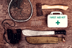 First aid kit surrounded by other survival gear.