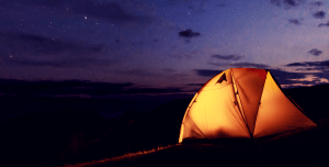 Medium-sized tent with a lamp inside sitting on the ground at night.