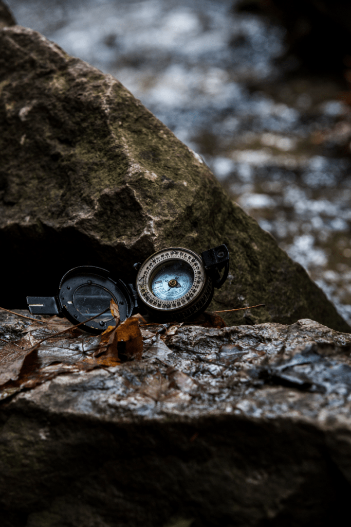 Open compass sitting against a rock.