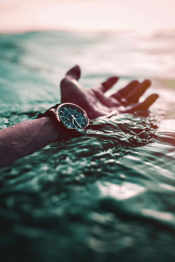 Arm in the water with a watch.