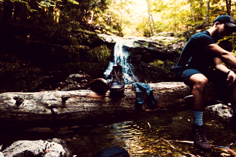 Mean sitting on log over stream with wet socks and boots laid out.