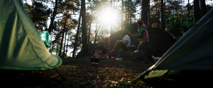 Group of campers sitting around food during sunset between 2 tents.