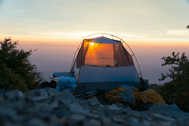 Tent on the top of a mountain with lots of gear stored out on the floor around it.
