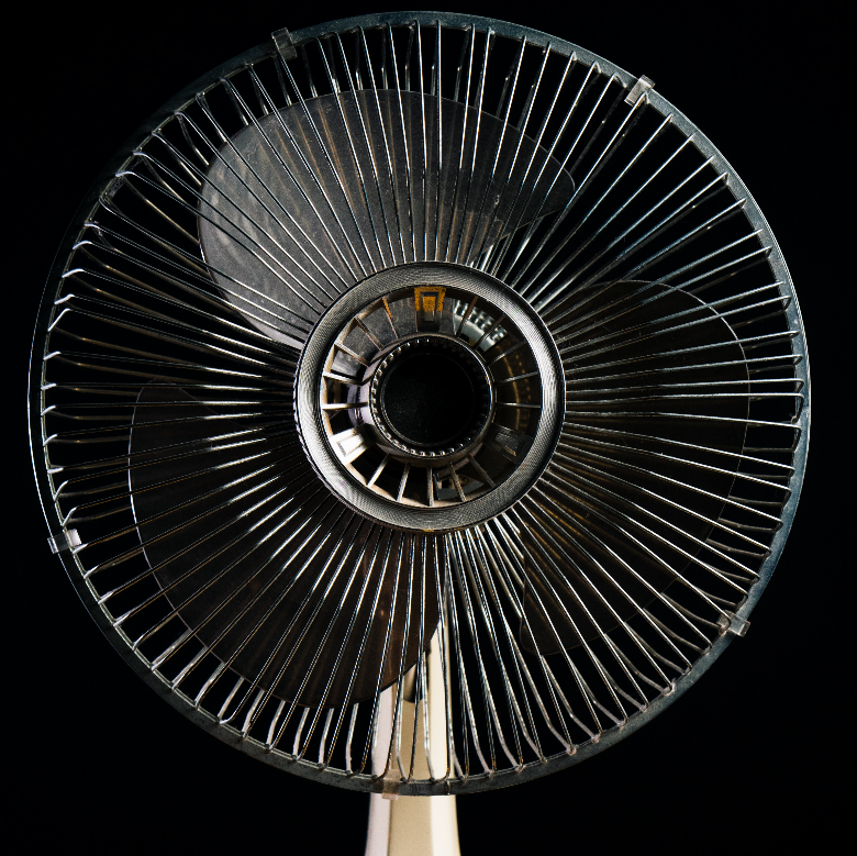 Close up, cropped photo of a fan on a black background.