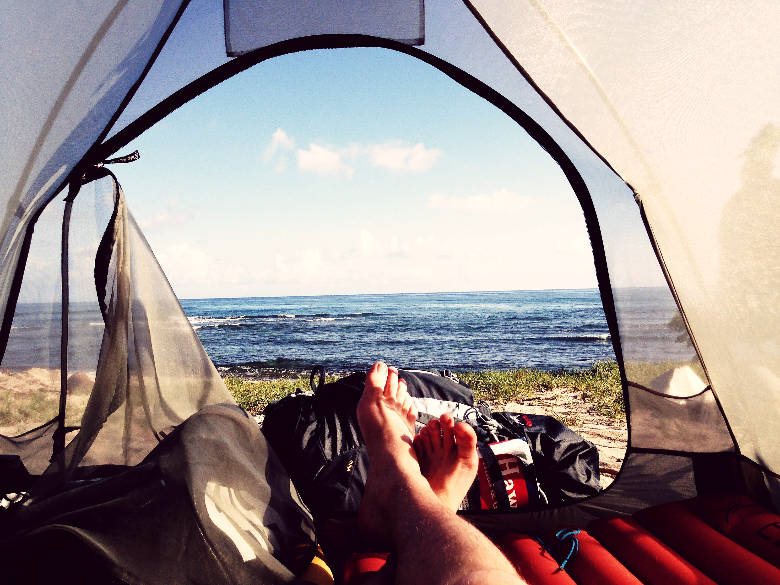 Open, well ventilated tent on the beach, open with bare feet sticking out.