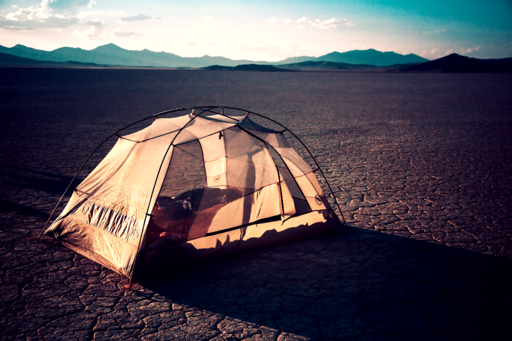 Mesh tent in the middle of the desert floor.