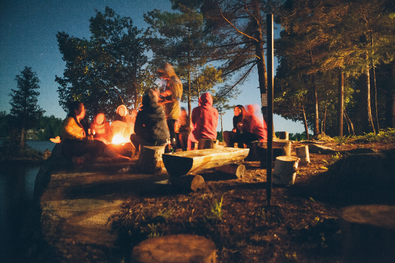 Group of campers surrounding a fire at twilight.