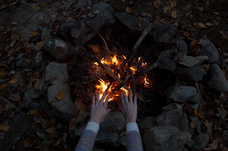 Hands over a bonfire at night.