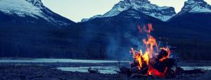 Campfire burning alone near a mountain range.