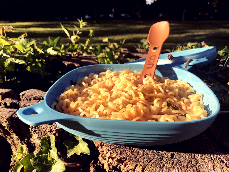 Close up of the UCO 4 piece with noodles inside sitting on a tree stump with spork.