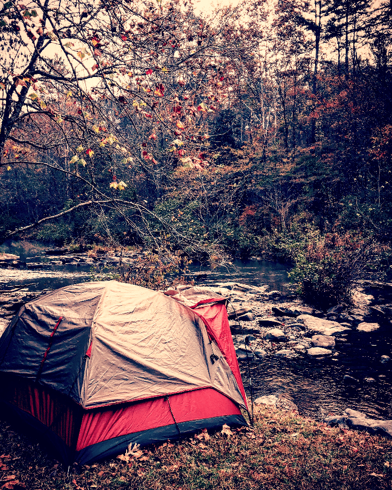 Tent with a rainfly on it sitting at the edge of a stream.
