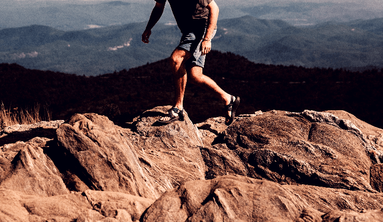 Guy jumping across rocks on a mountain wearing camp sandals.