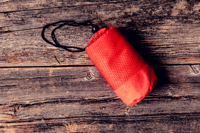 A light red carry sack resting on the floor.