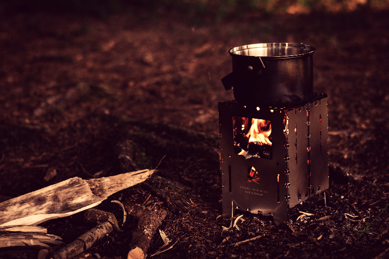 Wood burning camp stove next to a pile of wood with a fire going on and a pot on top.