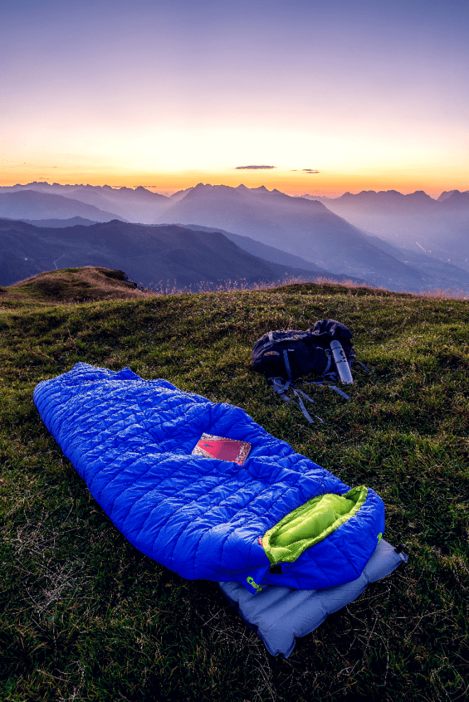 Sleeping bag on the top of a grassy mountain near a duffle bag.