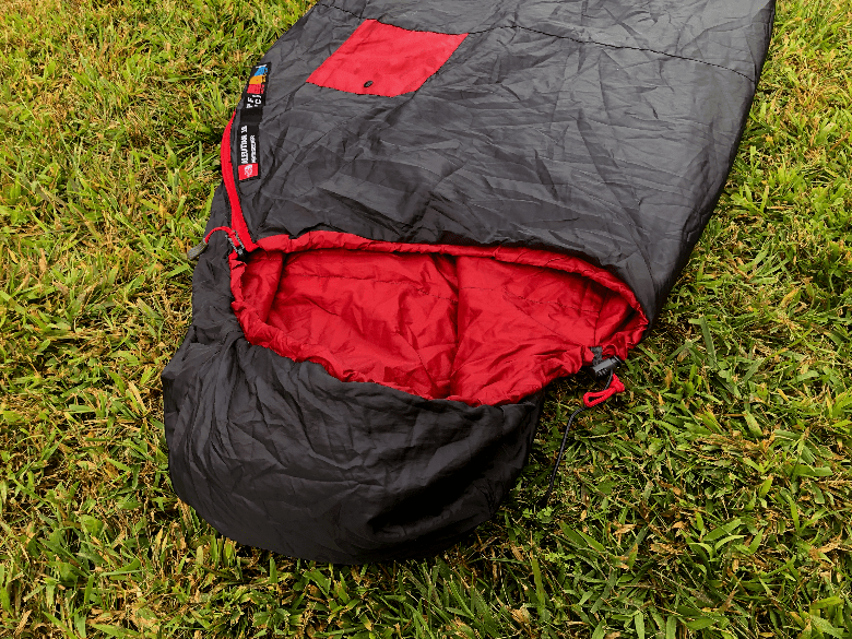 The hood of a mummy sleeping bag lying down in the grass.