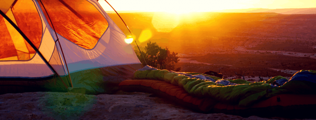Tent on the edge of a mountain at sunrise or sunset with a sleeping bag.