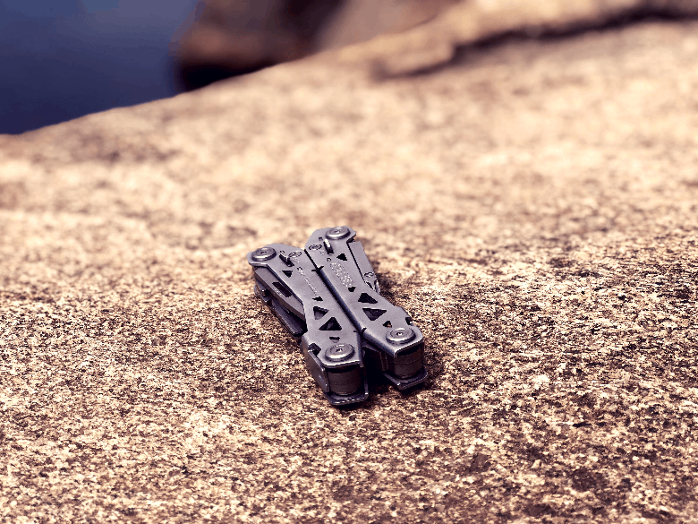 Foldable multitool closed up and sitting on a rock near the water.
