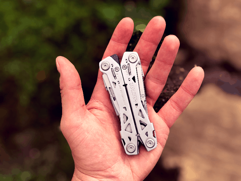 Closed multitool in my hand over some rocks and shrubs.