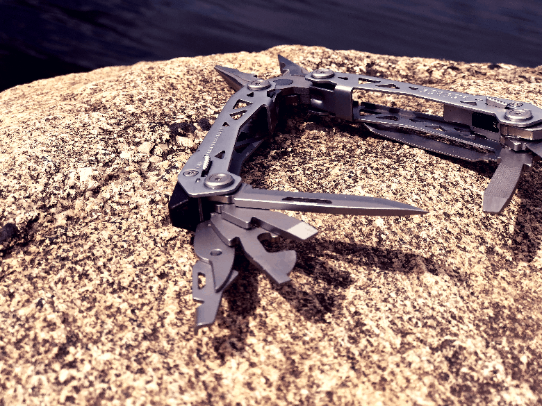Multitool with tools open and staggered on a rock near the water.