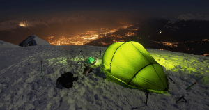 Tent at the top of a mountain at night in the snow with city lights nearby and a tent light on.