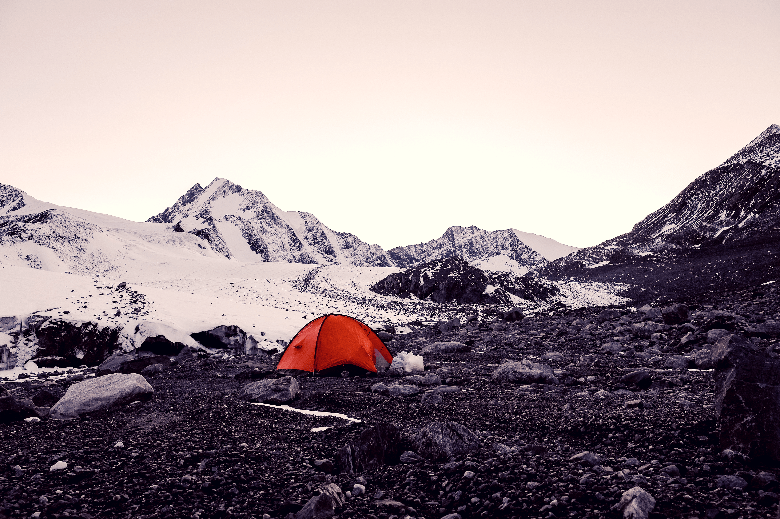Tent in cold environment on top of rocks near mountains.