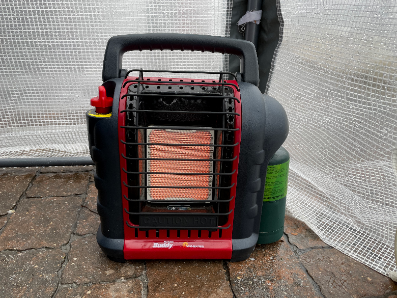 Mr. Buddy heater with a propane tank sitting in front of a wet tent.