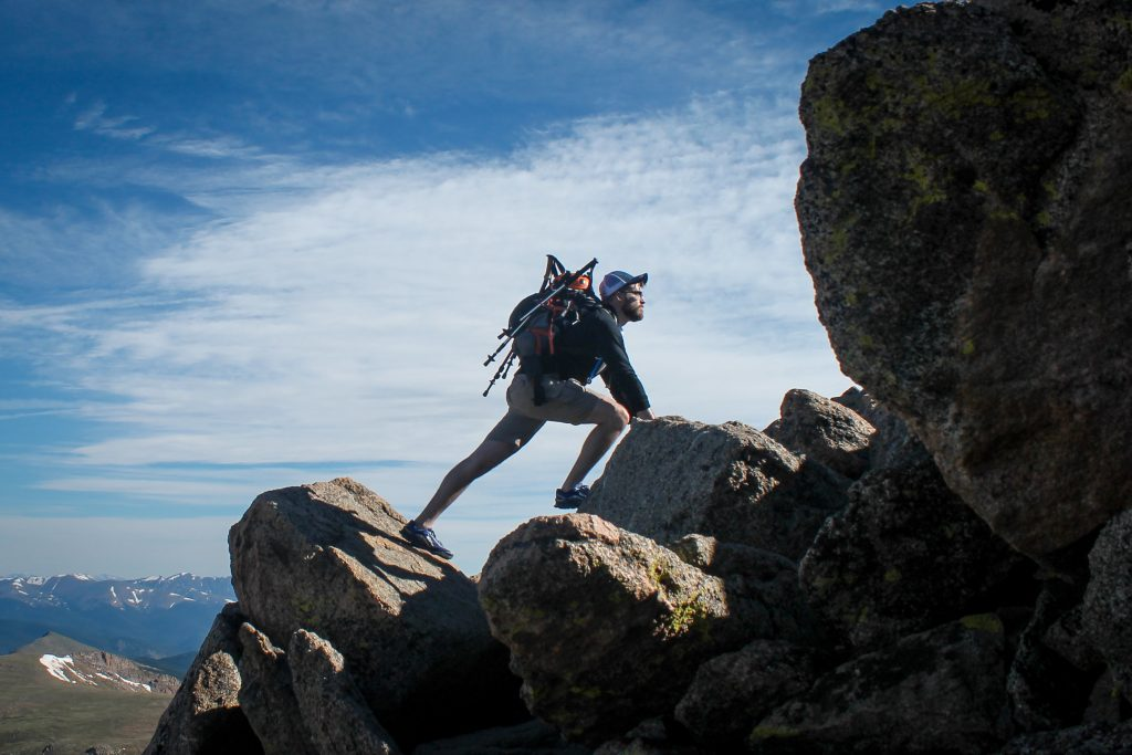 Man climbing over boulders with a backpack and folded trekking pole on his back.