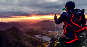 Man sitting on the edge of a cliff looking at the sunset with trekking poles.