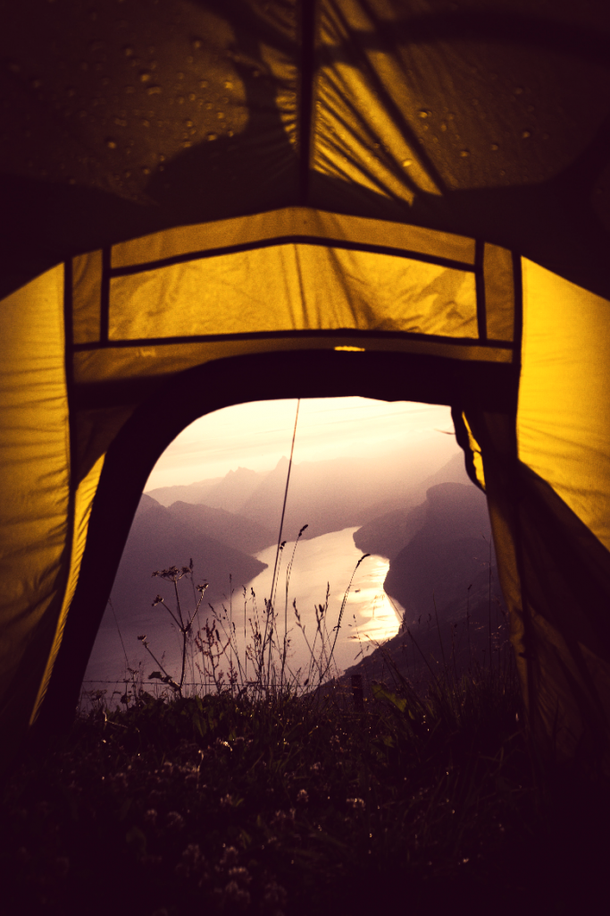 Point of view from inside a tent with rain on the roof at the top of a cliff.