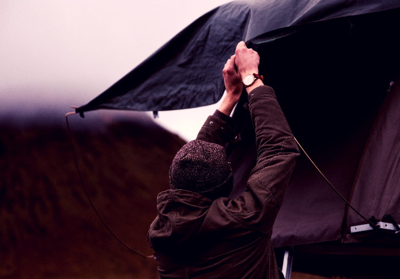 Person securing a rainfly in cloudy weather.