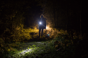 Woman from slightly far away looking toward camera with a flashlight on path in between trees.