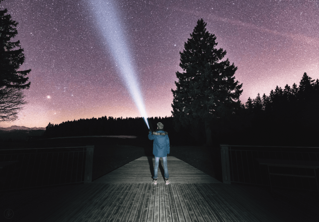 Man pointing a flashlight beam into the night sky on a boardwalk plank near some trees.