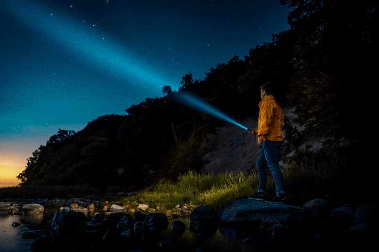 Person in rain jacket near the water on rocks shining a flashlight into the sky.