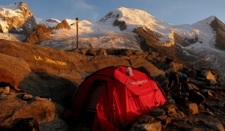 Tent sitting at the base of a mountain with snow in the background.