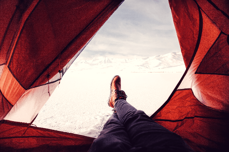 POV of person sitting with his legs and boots crossed outside of a tent.