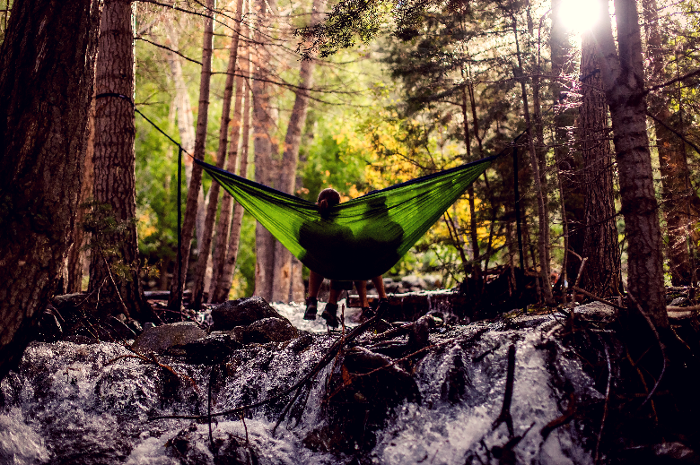 Hammock holding two people swinging over a stream and waterfall between two trees.