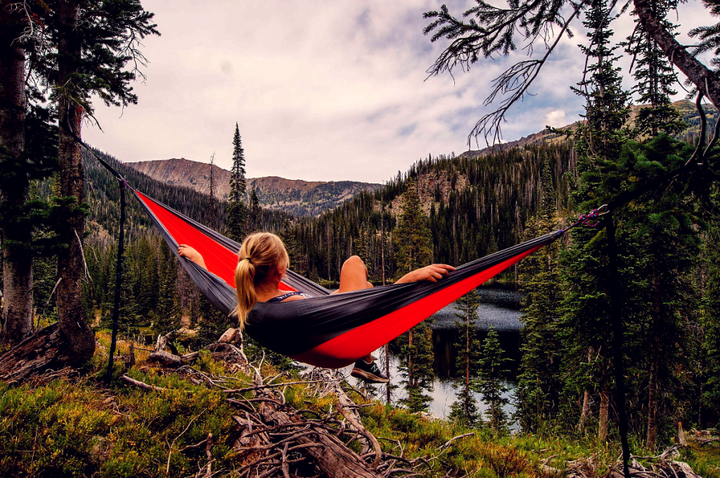 Woman sitting in hammock facing away looking at mountains with tons of trees.