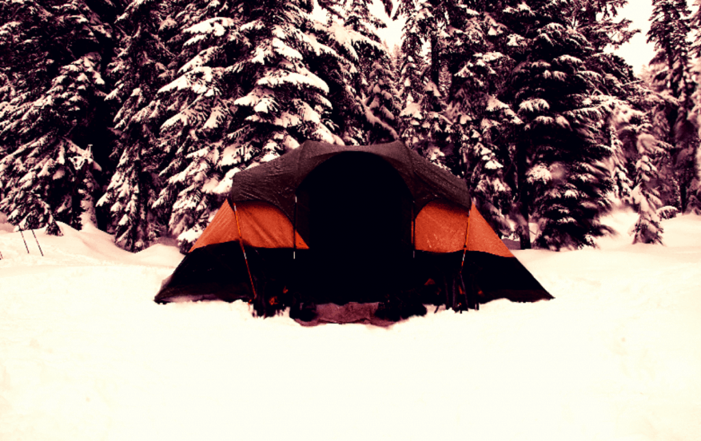 Picture of tent sitting in the snow in front of some trees.