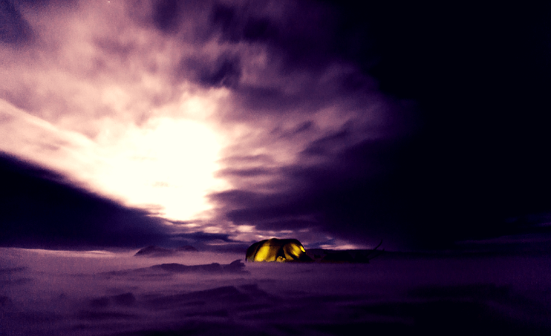 Tent sitting in the distance at night through the misty cold.