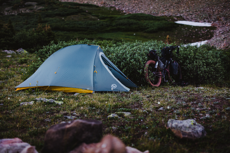 Tent sitting on the edge of a bush sitting right in front of a bike.