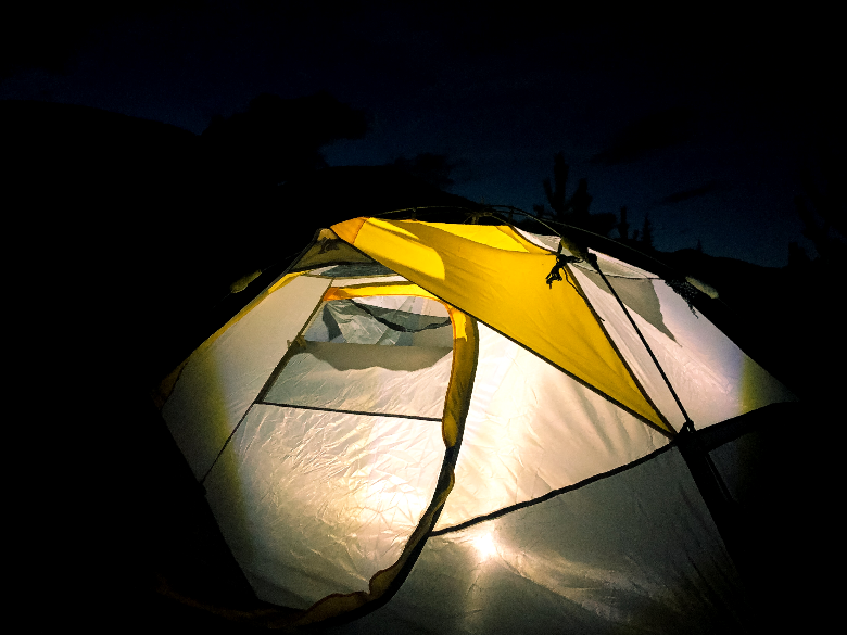 Tent sitting in the darkness with a light on inside the cabin.