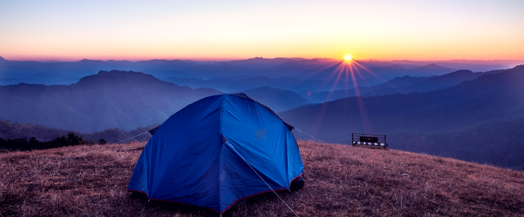 Tent sitting on the top of a hill near mountains away from the sunset.