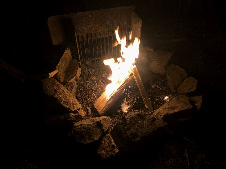 Burning camp fire inside fire ring with small paper inside.