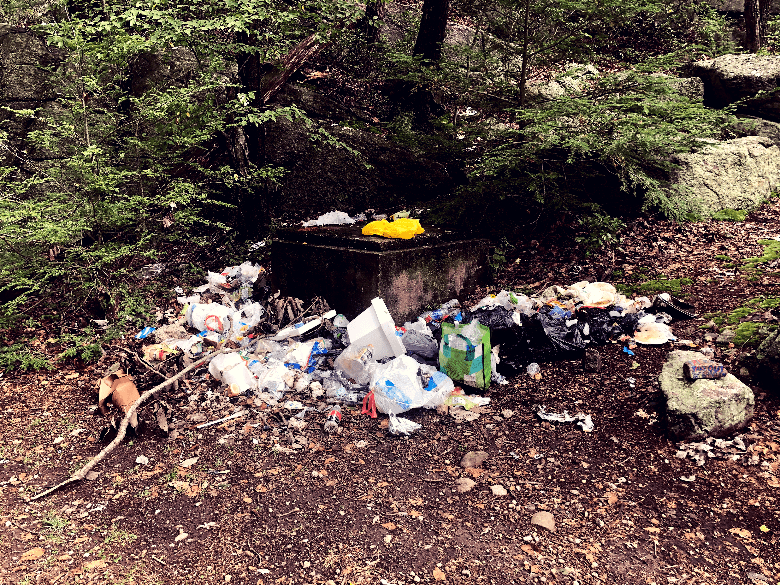 Lots of garbage piles around an apparent concrete block on a trail.