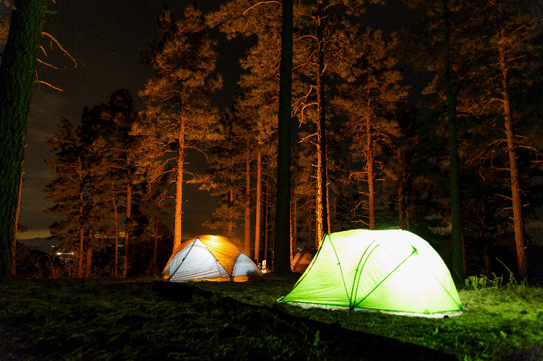Two tents at night, with lights inside.