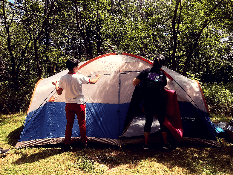 Two campers finishing setup for a 10 person tent.