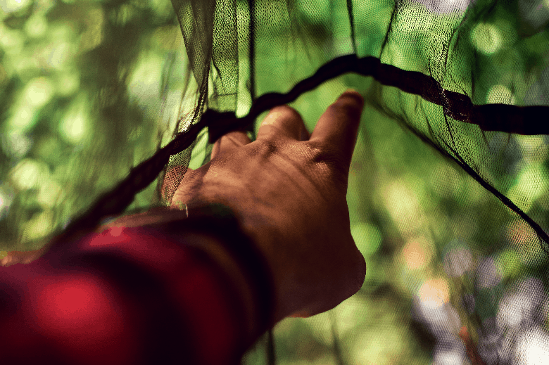 Hand reaching out to touch a dense hammock net from the inside.