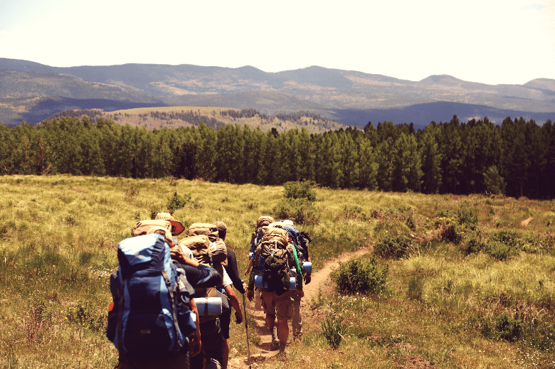 Group of backpackers walking through an open, grassy field.