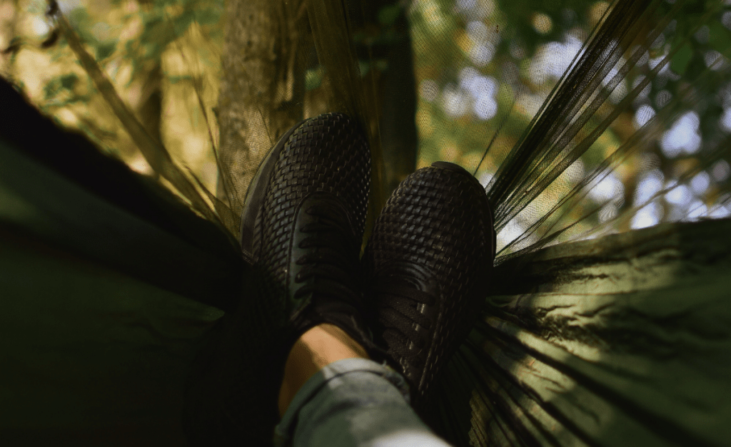 Pair of shoes, legs crossed, lying in a netted hammock.